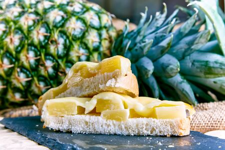 A pineapple and cheese sandwich on a slate plate. Reklamní fotografie