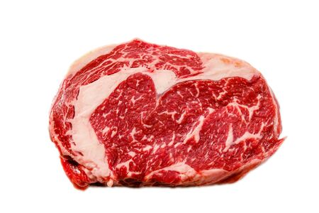 A rib eye steak of marbled grain-fed beef lies on a white background. Isolated. Stockfoto