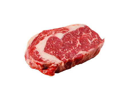 A rib eye steak of marbled grain-fed beef lies on a white background. Isolated. Фото со стока