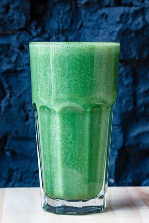 Green smoothie made from herbs and vegetables in a large glass glass against a dark stone wall Stock Photo