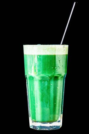 Green smoothie made from herbs and vegetables in a large glass glass on a black background, isolated