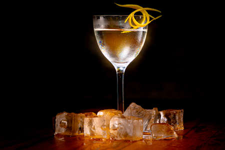 Vodka with ice and lemon in a glass on a high leg is on the bar Reklamní fotografie