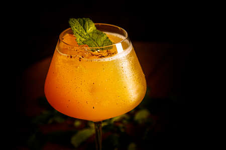 Orange cocktail with mint and ice poured into a glass