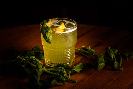Green alcoholic cocktail with Basil is poured in a glass on the bar.
