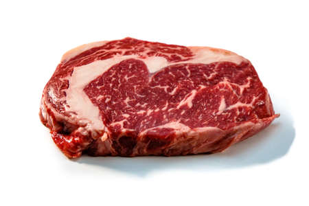 Ribeye. A raw marbled beef steak sits on a white background with a shadow.