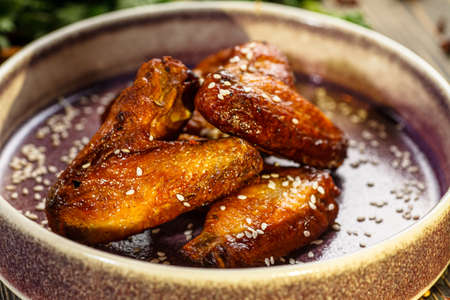 Baked chicken wings in sauce and sprinkled with sesame seeds are on a plate Stock Photo
