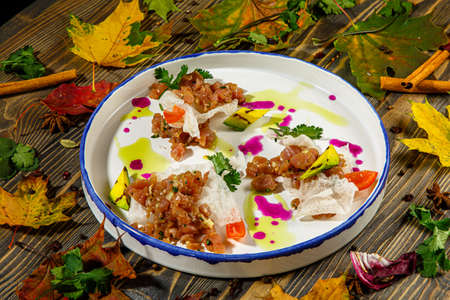 Beef tartare with rice chips and vegetables is on the plate Фото со стока