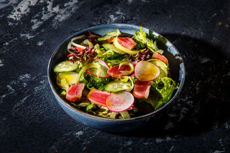 Salad of lettuce leaves, fried tuna, cucumbers and radishes is on the plate