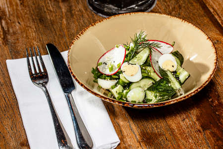 Cucumber, radish and egg salad is on the plate