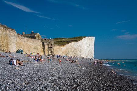 bathers: Bagnanti su una spiaggia a Seven Sisters scogliere Editoriali