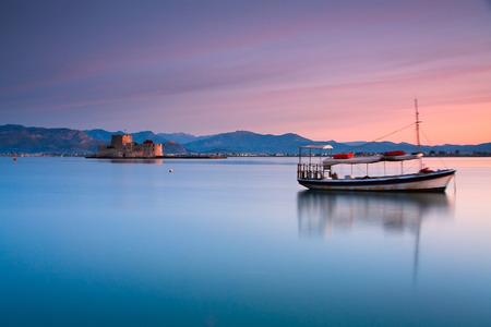 Boat and Burtzi castle in Nafplio, Greece.