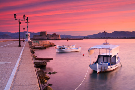 Fishing boats and Bourtzi castle in the Nafplio harbour in Peloponnese peninsula, Greece.