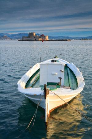 bourtzi: A fishing boat in Nafplio harbour and Bourtzi castle, Greece.