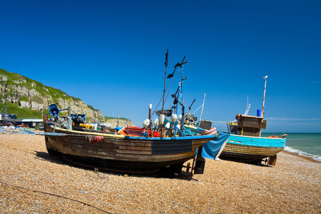 Fishing boats on the beach in Hastings harbour, East Sussex, UK. Фото со стока