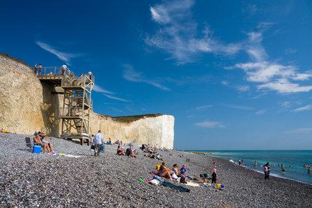 bathers: Bagnanti a Birling Gap a Seven Sisters scogliere in East Sussex, Regno Unito. Editoriali