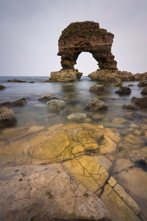 Rock arch on the coast of Tyne and Wear, UK. Фото со стока