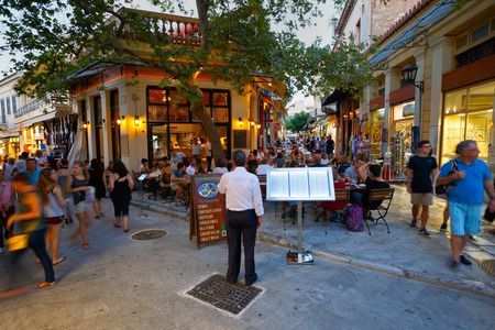 A man inviting customers to a restaurant in the street in Plaka, Athens Редакционное