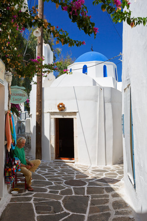 shop keeper: Shop keeper in front of his shop in a treet with a small church in Naousa village on Paros island, Greece