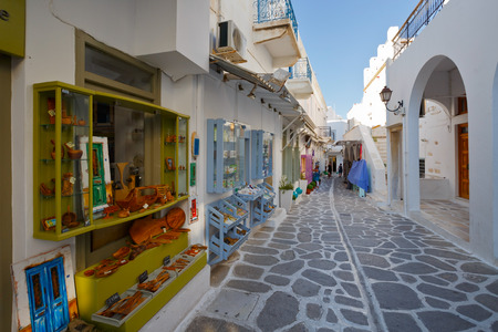cycladic: Street with shops and traditional architecture in the old part of Parikia, the capital and main port of Paros island in Greece Editorial