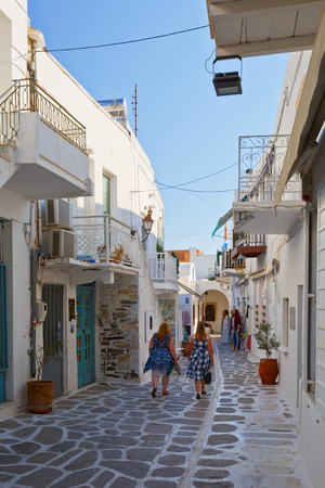 cycladic: Two women walking in a street with shops and traditional architecture in the old part of Parikia, the capital and main port of Paros island in Greece