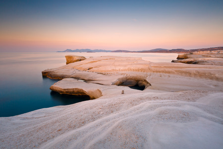 Coastal scenery with pale volcanic rocks near Sarakiniko beach in Milos island, Greece. Kimolos island can be seen in the distance. 免版税图像