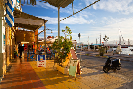 seafronts: Street view of the coffee shops, bars and restaurants and the harbour of Aegina town, Greece Editorial