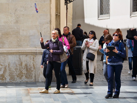 Tourist guide and a group of foreign tourists in the old town of Bratislava. Редакционное