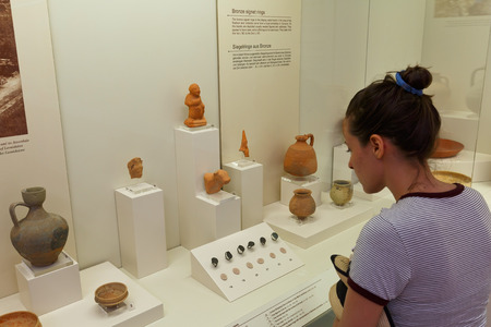 greek pot: Visitor looking at terracottas in the Archaeological museum of Olympia.