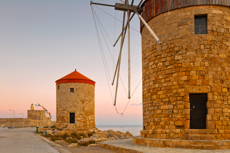 Windmills and fort of St. Nicholas in town of Rhodes. Stock Photo