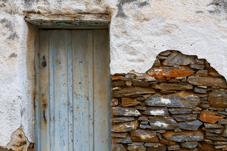 and worn out: Old wall with a door and visible stonework.