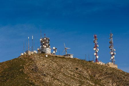 satelite: Telecommunication antenas on a hilltop over Ermoupoli town on Syros island in Greece. Editorial