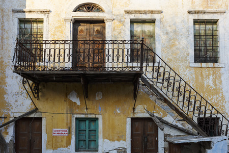 Facade of an old abandoned building in Kalymnos town, Greece.