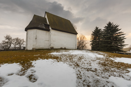 Small Gothic church near a cemetary in a village of Turiec Region in northern Slovakia in winter.