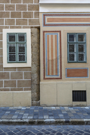 Wall and windows of historical buildings in the old town of Buda in Budapest.