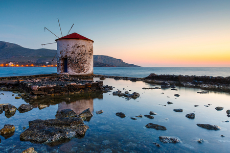 Sunrise landscape with a windmill in Agia Marina village on Leros island in Greece. Imagens