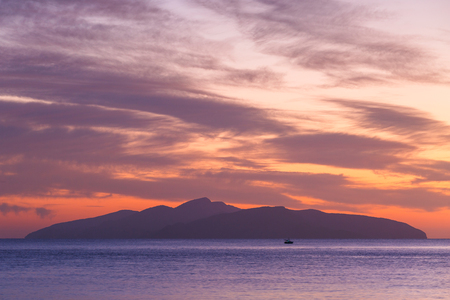 View of Hydra island against colorful morning sky from Spetses, Greece.