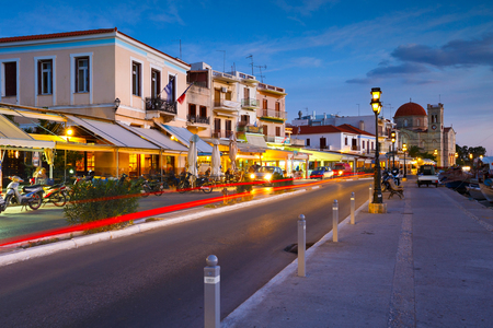 Aegina, Greece - November 23, 2015: Street view of the coffee shops, bars and restaurants and Ekklisia Isodia Theotokou church on the seafront of Aegina town, Greece.
