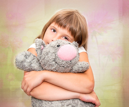 Girl dreaming with grey plush toy cat photo