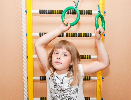 Teen girl near sport ladder at home photo