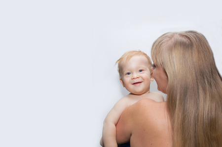 Young blond mother carries her smiling son photo
