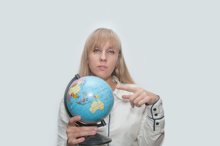 Young Blond woman shows globe in hands photo