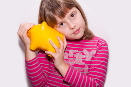 teen girl with yellow pig moneybox isolated