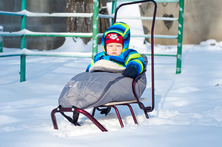 Little Baby boy sits on sled sunny snowy winter weather photo