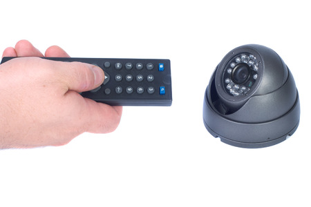 close circuit camera: Man`s hand with remote and security camera isolates white