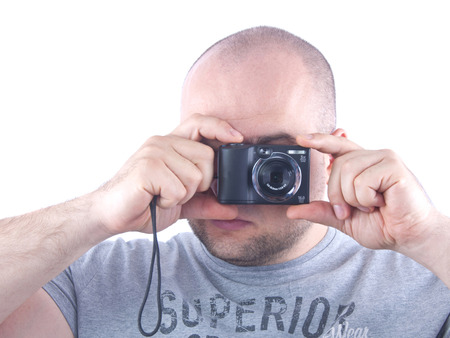 photocamera: young man with small black photocamera in hands near face isolated white