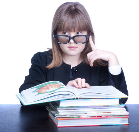 Girl in glasses wearing black uniform sits at a table in front of her stack of books. Girl looks left