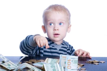 cash money: El niño pequeño con el pelo rubio y ojos azules sentado en la mesa y cuenta el dinero.