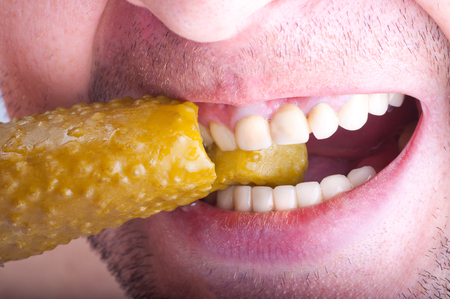 marinated gherkins: Man tries delicious pickles. Close-up. Stock Photo