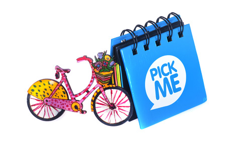 bike cover: little blue notebook next to which is a small bicycle painted, handmade, white background Stock Photo