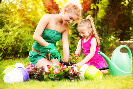 Beautiful mother and daughter planting flowers in the garden photo